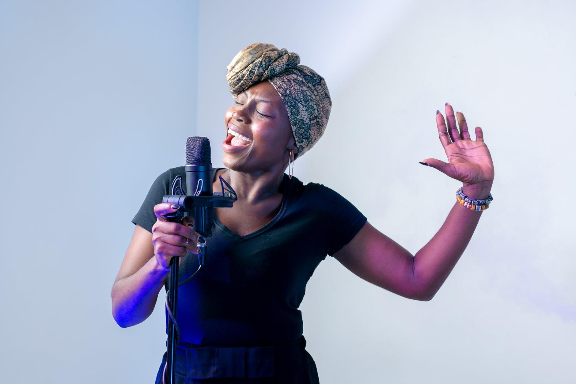 photo of woman singing in music studio