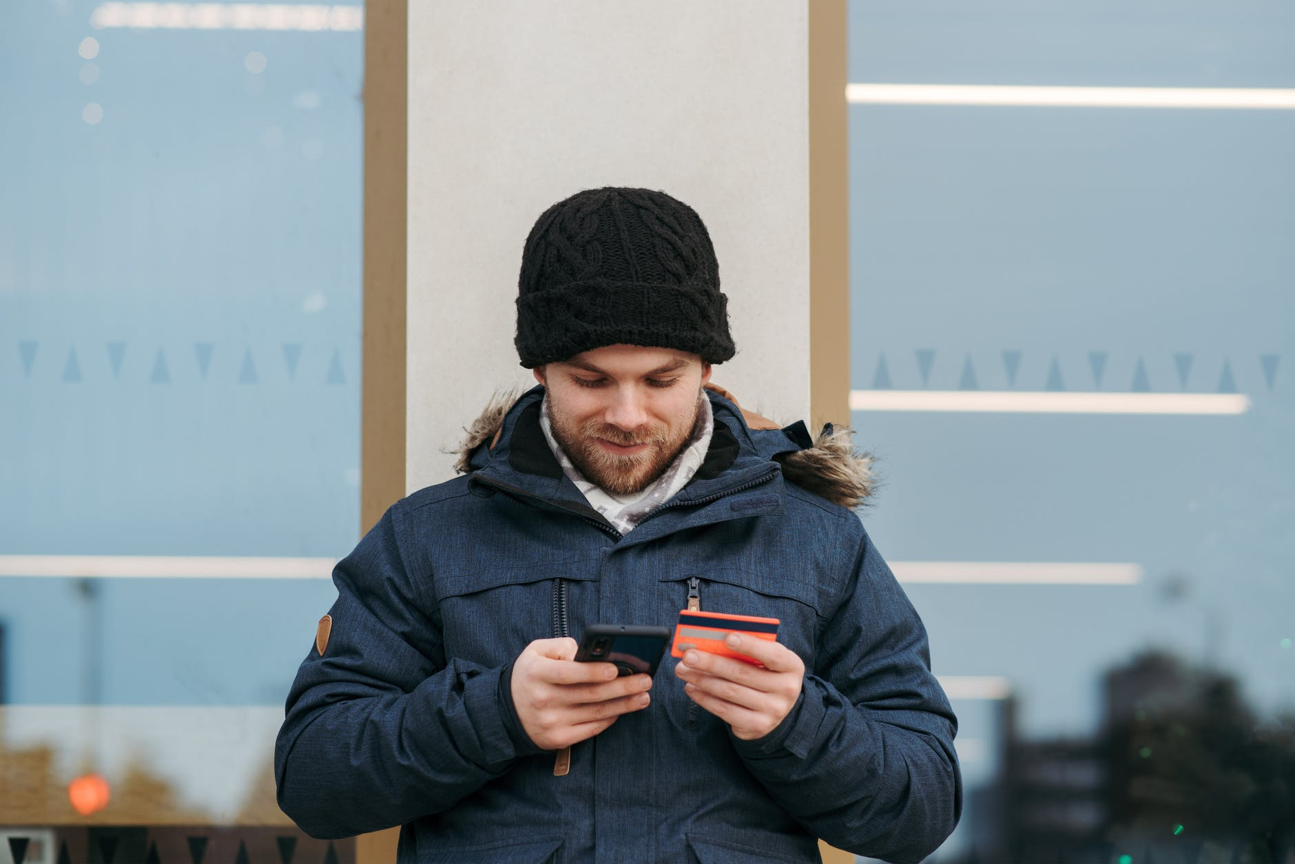 cheerful man entering details of credit card on smartphone on street