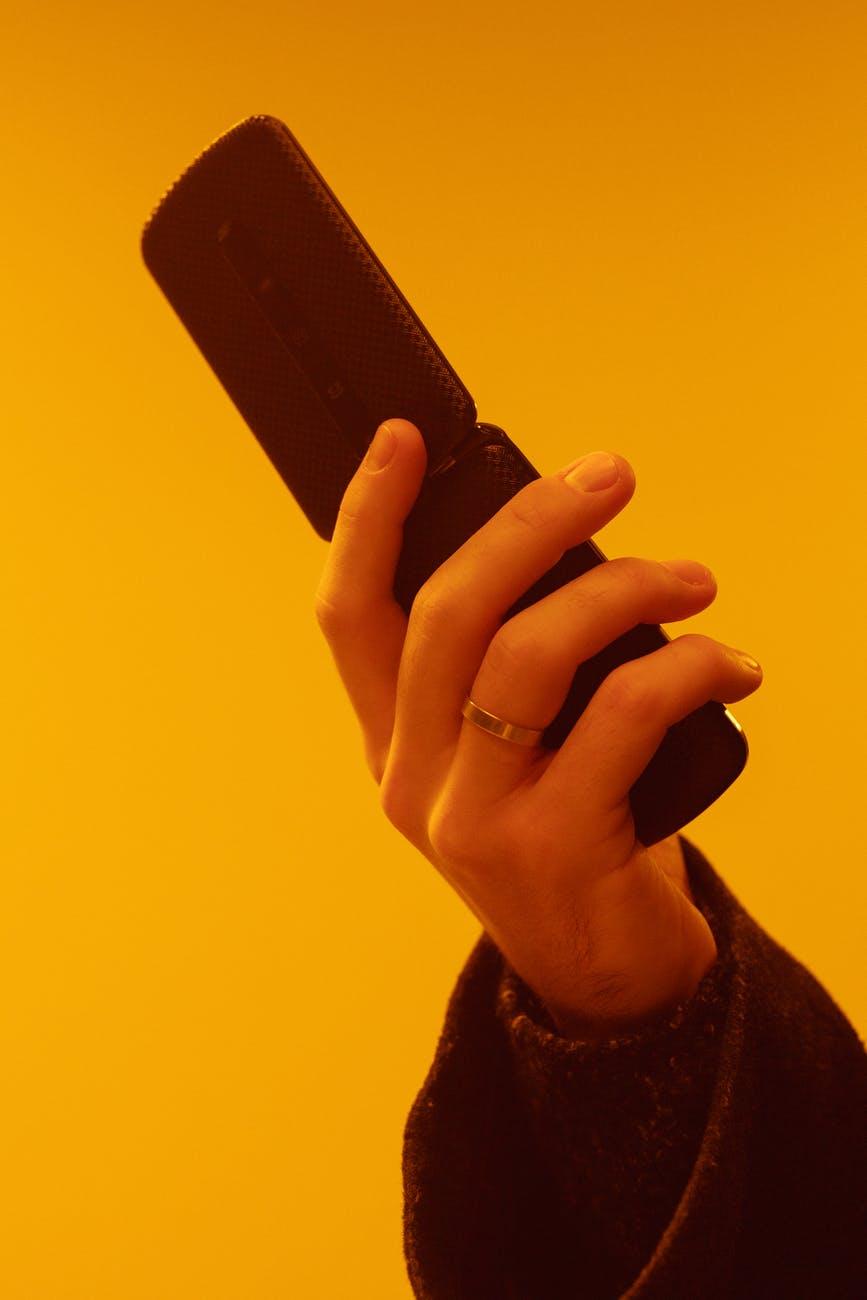 person holding black rectangular device